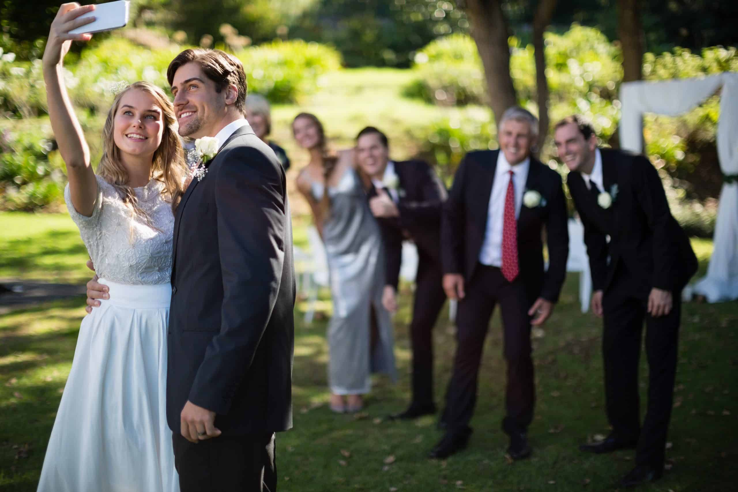 Couple taking selfie with guests during wedding in park