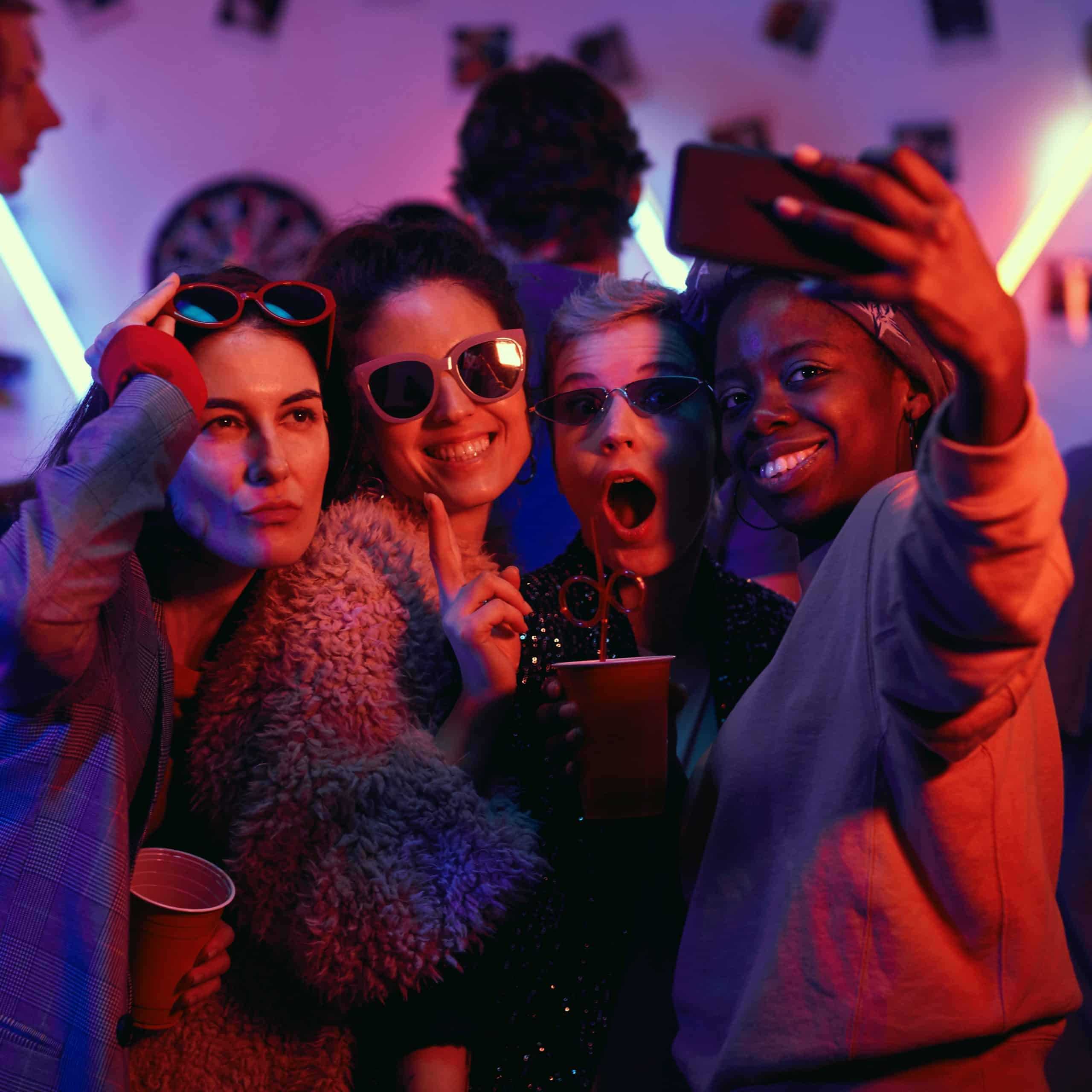 Group of happy girls standing and making selfie on mobile phone while having fun at disco party